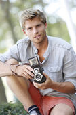 Trendy photographer using vintage camera — Stockfoto