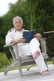 Man reading book in pool deck chair — Stock Photo