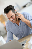 Businessman in office talking on phone — Stock Photo