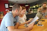 Students choosing dish from menu — Stock Photo