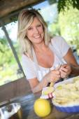 Beautiful mature woman cooking pastry — Stock Photo