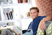 Man in apartment reading book — Stock Photo