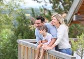 Family enjoying vacation in log cabin — Stock Photo