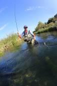 Fisherman catching rainbow fish — Stock Photo