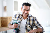 Man at home using electric drill — Stock Photo