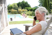 Woman talking on phone by swimming-pool — Stock Photo