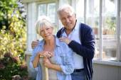 Couple standing by greenhouse in garden — Stock Photo