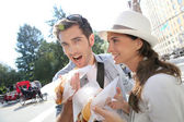 Tourists in New York eating hot dogs — Stock Photo