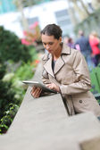 Businesswoman in park with digital tablet — Stock Photo