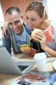 Roommates eating sandwich in front of laptop — Foto de Stock