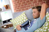 Man at home taking nap in sofa — Stock Photo