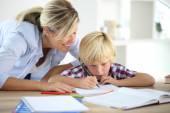 Mom helping boy to do homework — Stock fotografie