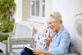 Senior woman reading book on bench — Stock Photo