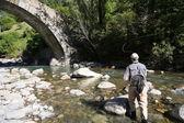 Fisherman fishing in mountain river — Stock Photo