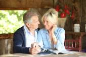 Couple in yard reading magazine — Stock Photo