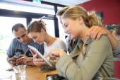 Friends in campus lounge websurfing with tablet — Stock Photo