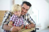 Father with kid measuring wood plank — Stock Photo