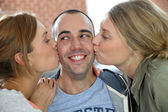 Guy being kissed by 2 girl friends — Stock Photo
