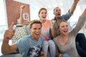 Roommates in apartment watching football game — Stock Photo