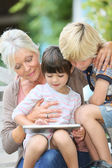 Grandmother with kids playing on tablet — Stock Photo