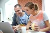 Roommates eating sandwich in front of laptop — Stock Photo