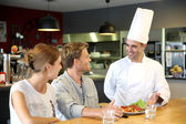Chef serving cooked dish to customers — Stock Photo