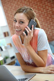Girl at home talking on mobile phone — Stock Photo