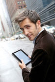 Businessman in Manhattan using tablet — Stock Photo
