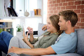 Couple in sofa and using tablet — Stock Photo