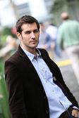 Businessman standing in city steet — Stock Photo
