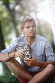 Trendy photographer using vintage camera — Stock Photo