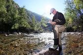 Flyfisherman choosing artificial fly as bait — Stock Photo