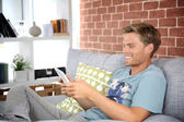 Young man using tablet in sofa — Photo