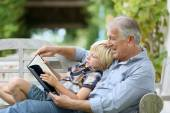 Grandfather reading book with grandson — Stock Photo