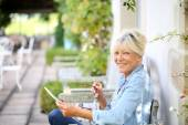 Woman relaxing outside and using tablet — Stock Photo