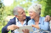 Senior couple connected on digital tablet — Stock Photo