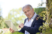 Man websurfing on tablet in garden — Stock Photo
