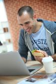 Student eating sandwich in front of laptop — Zdjęcie stockowe