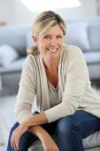 Attractive woman sitting in sofa — Stock Photo
