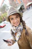 Girl in street using smartphone — Stock Photo