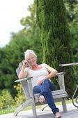 Woman talking on mobilephone in backyard — Stock Photo