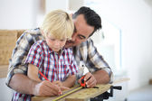 Father with kid measuring wood plank — Foto de Stock