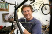 Man in workshop fixing bike frame — Stock Photo