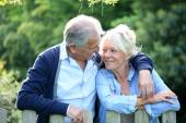 Senior couple standing by fence — Stock Photo