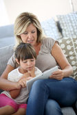 Mother and daughter playing on tablet — Stock Photo