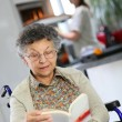 Elderly woman reading book — Stock Photo #64674709
