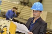 Engineer in factory reading blueprint — Stock Photo