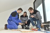 Carpenter with trainees installing wooden floor — Stock Photo