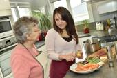 Home carer cooking dinner — Stock Photo