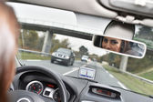 Woman looking at rear view mirror — Stock Photo